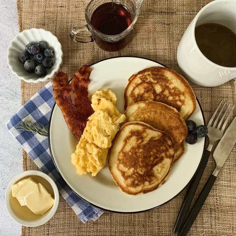Amerikanisches Frühstück mit Pancakes, Ei und Speck
